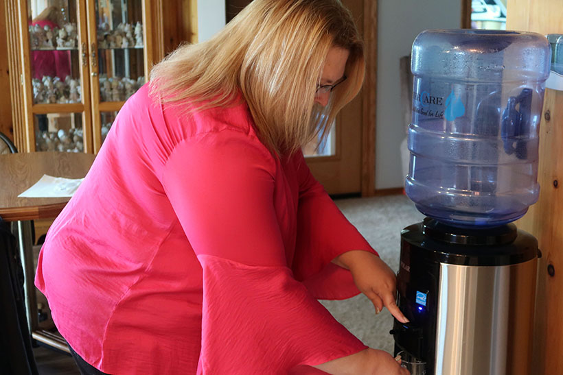 Erika Balza fills up a glass with water in her Kewaunee County home