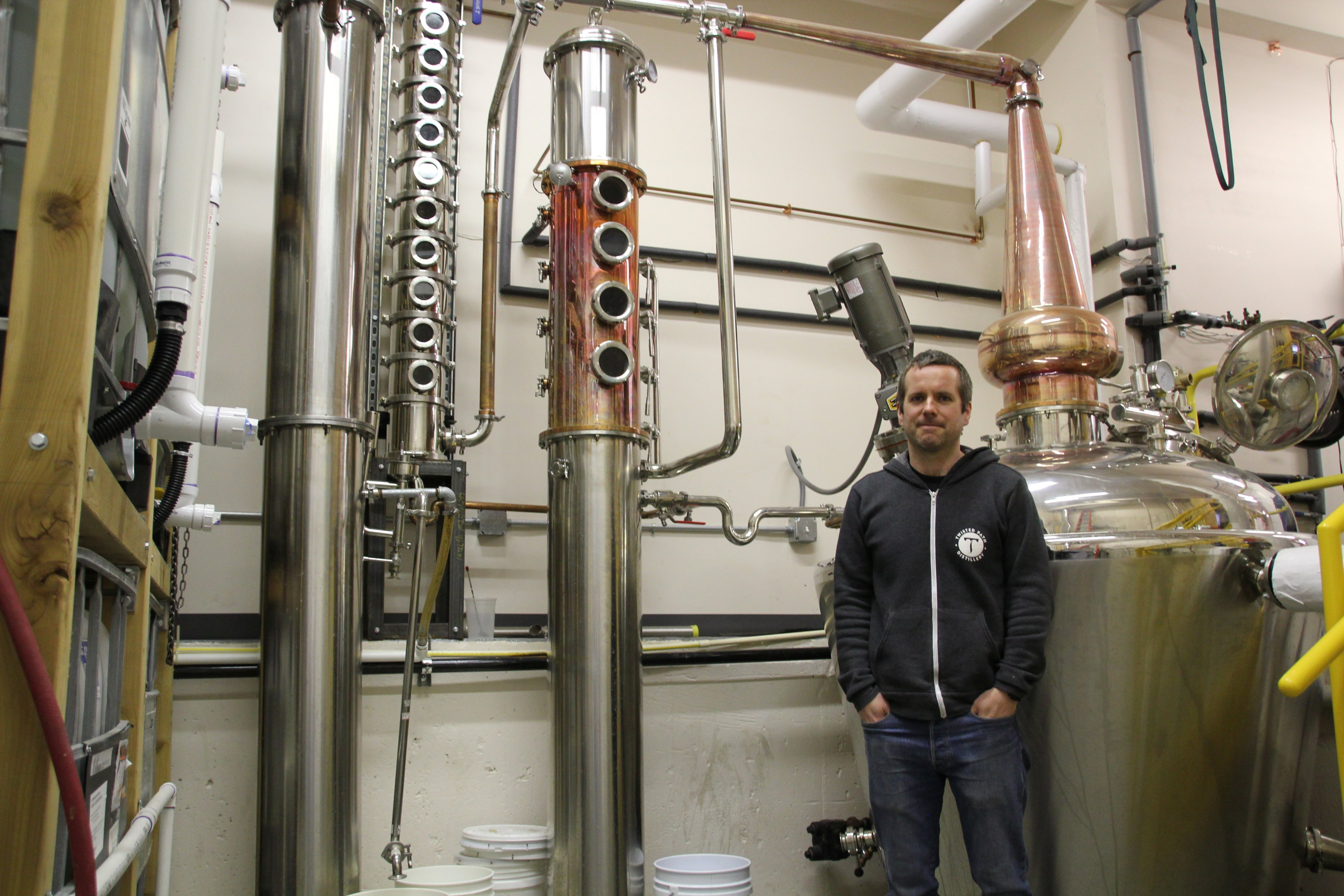 Brian Sammons stands in front of one of his stainless steel distillers.