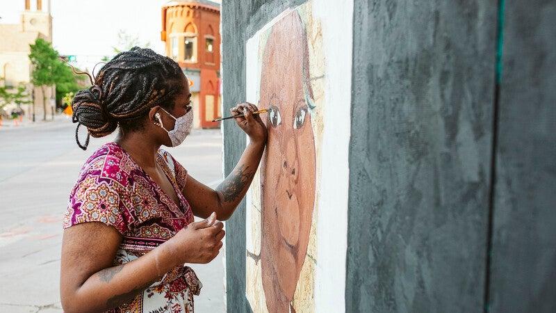 Artist Cassie Pierce paints a mural on Short Stack Eatery