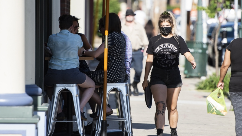 waitress wears a mask while serving customers outside