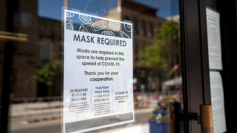 """A sign on a glass door says """"mask required"""""""