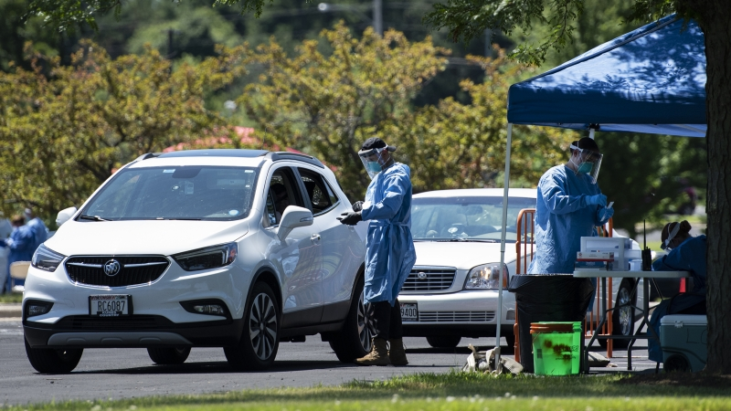 A man in a blue medical gown approaches a white SUV to administer a test