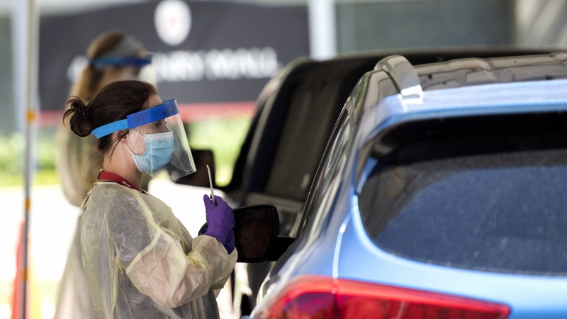 a woman in a face shield holds a swab as she speaks to someone through their car window