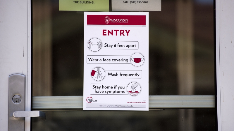 A sign hangs on a glass door explaining COVID-19 safety to those who enter