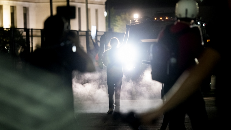 smoke surrounds a protester with a fist raised. they are seen in silhouette illuminated by a bearcat headlight.