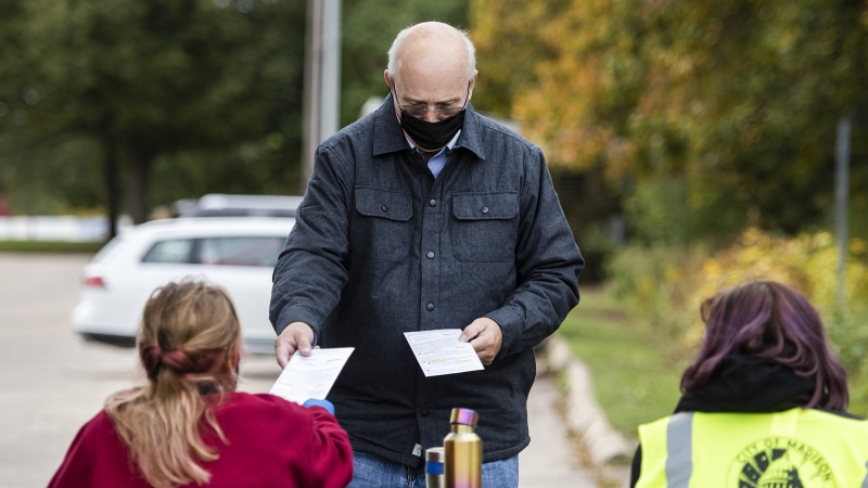 A man hands ballots to workers at a park table