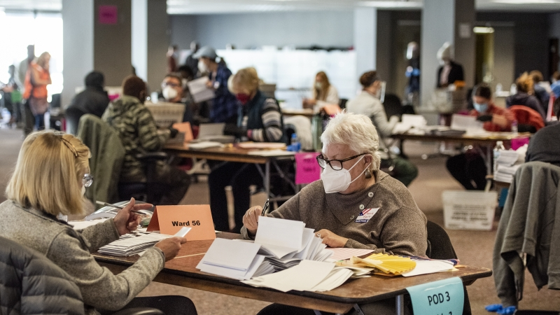two workers sit at a table and sort ballots