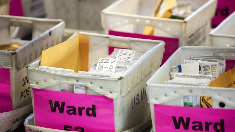 white boxes filled with ballots are labeled with ward numbers
