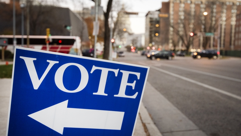 """a blue sign says """"VOTE"""" with an arrow"""