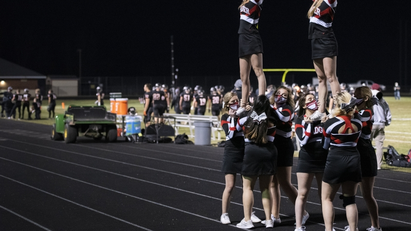 cheerleaders make a formation as they perform on a track surrounding the football field
