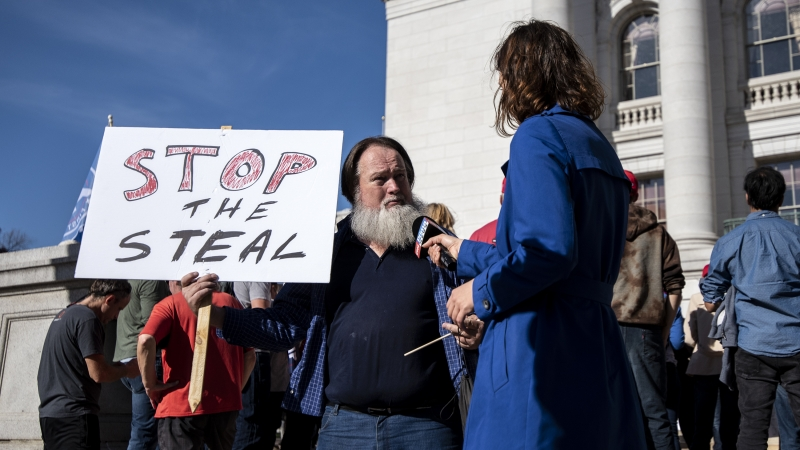 "A man holds a sign that says ""stop the steal"""