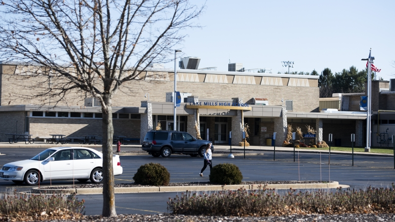 A person walks in the parking lot in front of Lake Mills High School.