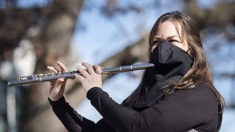 A woman plays a flute through a hole in a black face mask