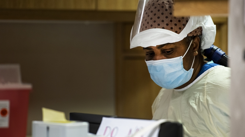 A woman in a mask with a large hood pulled up onto her head exits a COVID-19 patient's room