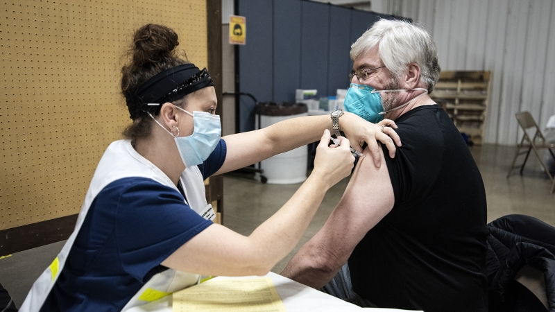 A nurse pulls up the sleeve of a man as she gives him a shot