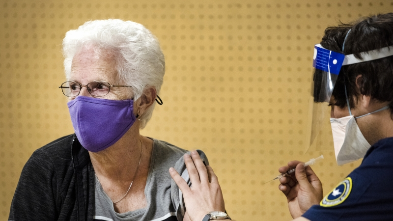 a woman in a purple face mask sits to receive her vaccine