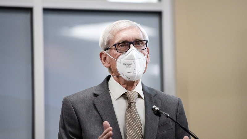 Gov. Evers speaks at a lectern while wearing a white face mask.