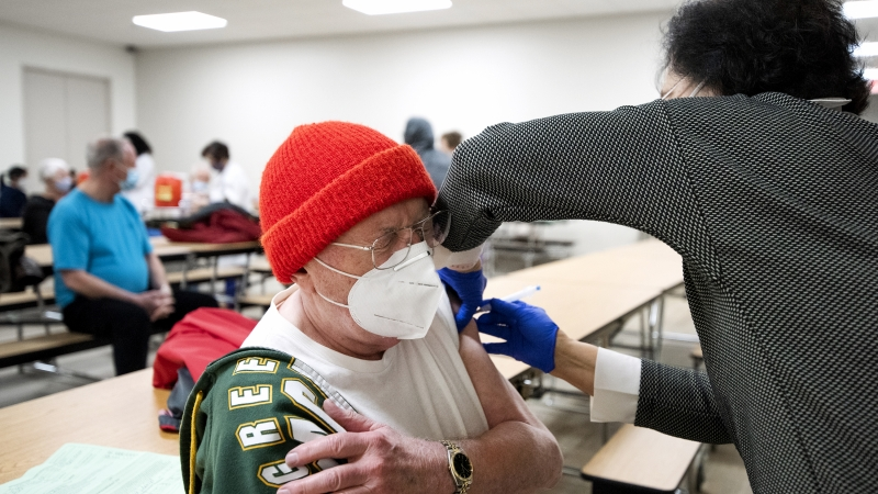 A man in closes his eyes as a vaccine is administered