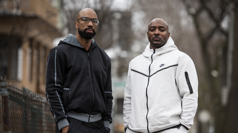 Two men, one dressed in black and the other dressed in white, stand outside on a Milwaukee sidewalk.