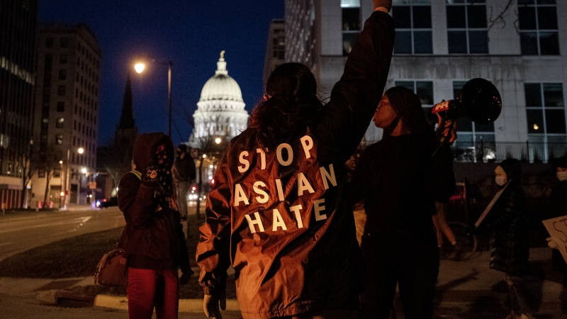 """""""STOP ASIAN HATE"""" is written on the back of a protester's jacket. The Wisconsin State Capitol can be seen in the background."""