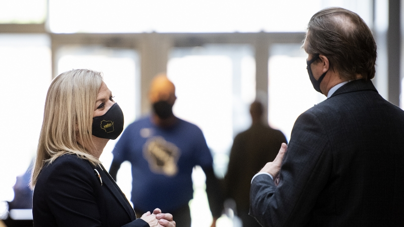 A woman in a face mask stands in a lobby as sun shines through windows behind her.