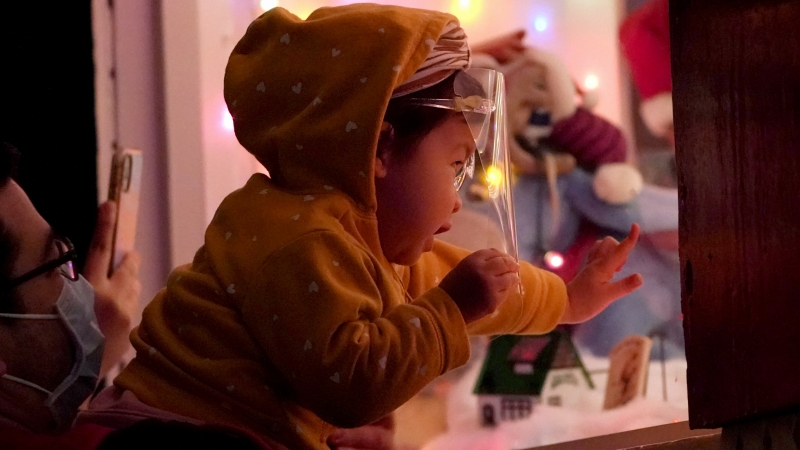 Meya McPalmer, 1, wears a face shield to protect against COVID-19 while peeking into the Christmas display