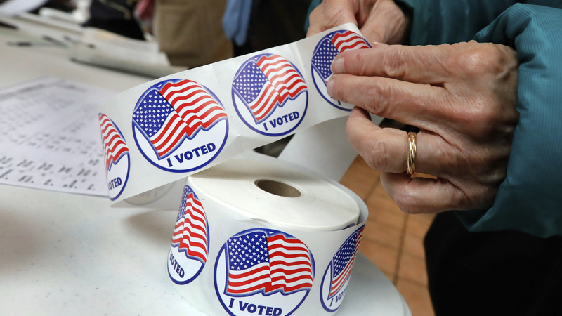 "A voter retrieves her ""I Voted"" sticker"