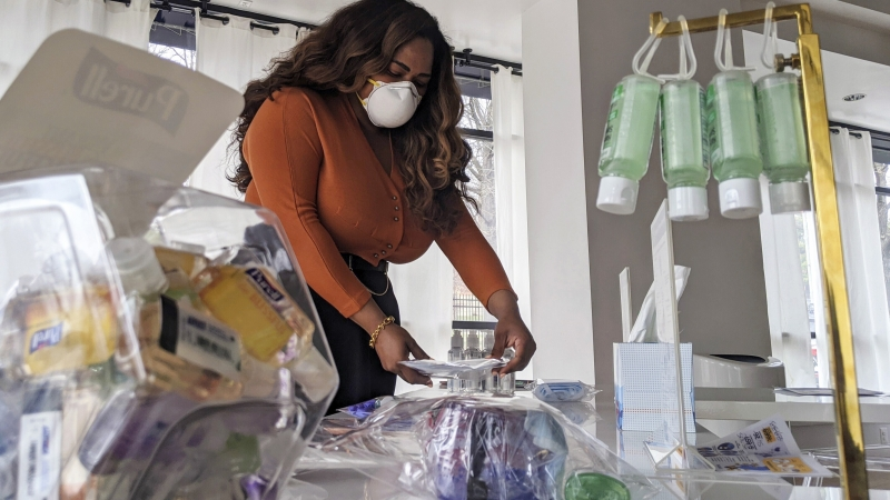 Adilisha Patrom organizes face masks, hand sanitizer and other supplies inside her pop up shop