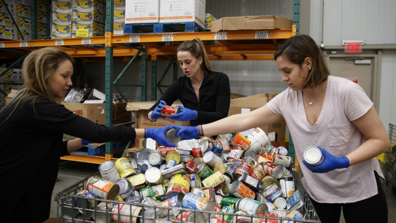 Katie Coerdt, Paige Dekker, and Caitlin Merely sort canned food as they wear disposable gloves at Capitol Area Food Bank