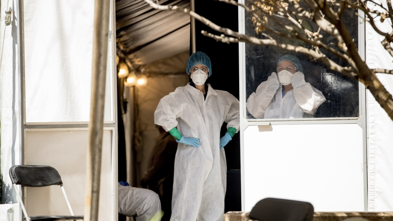 Medical workers stand at the door to a coronavirus testing site