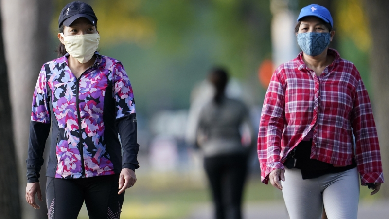 Thu Huynx and Trang Ngyen walk along a park trail while wearing face masks to help prevent the spread of COVID-19