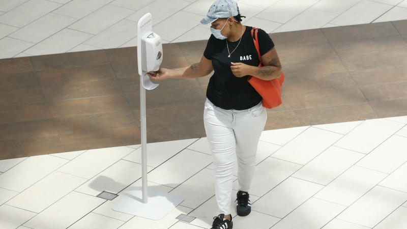 A person stops for some hand sanitizer at the Arden Fair Mall