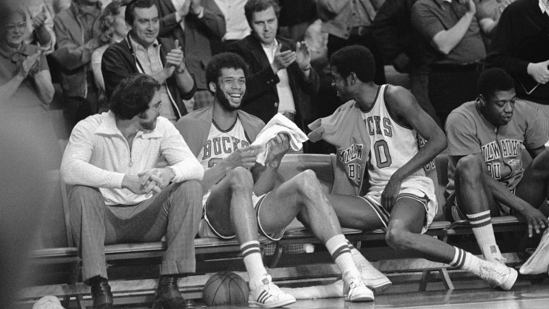 Bucks center Kareem Abdul-Jabbar laughs as he sits on bench