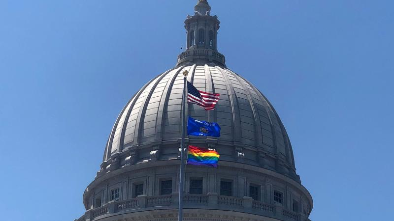 """a rainbow flag flies over the state Capitol in recognition of """"Pride Month"""""""