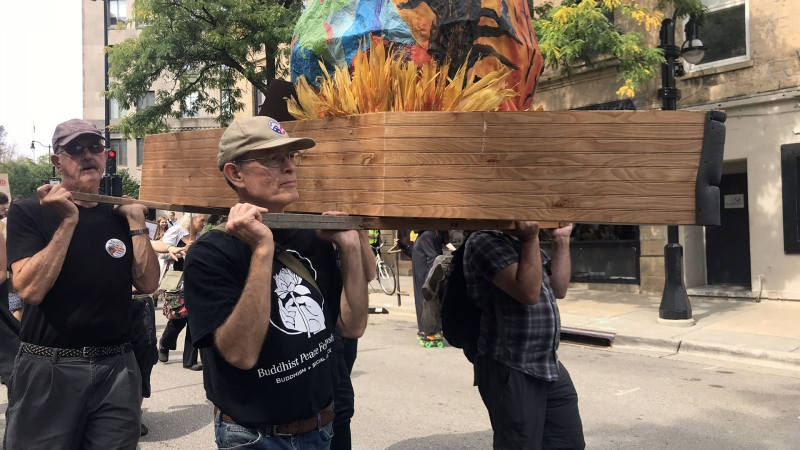 Pallbearers carry a coffin for a flaming Earth