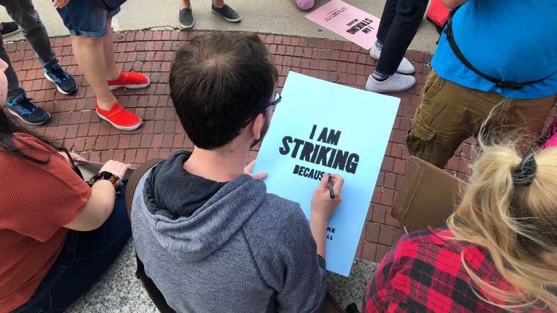 """An attendee of a global climate strike rally in Milwaukee writes on a sign that says """"I am striking because."""""""