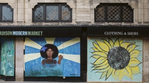 Artwork by Sapphina and Zaria is displayed on boarded up store windows on State Street