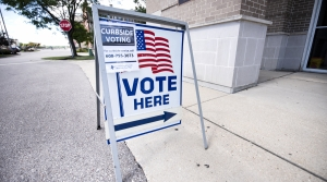 "A ""Vote Here"" sign has an added sign about curbside voting"