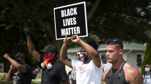 """A protester holds up a """"Black Lives Matter"""" sign as they march"""