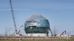 Cranes surround a large globe under a blue sky