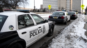 Three Milwaukee police cars are parked on a snowy street.