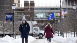 A girl wears a Marquette hat while walking in front of an elevated walkway on the campus. Snow is on the ground.
