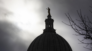"A silhouetted ""Wisconsin"" statue is seen in front of dark clouds."