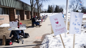 "Signs say ""We Love Our Students"" and ""In It For The Kids"" as teachers give virtual lessons outdoors."