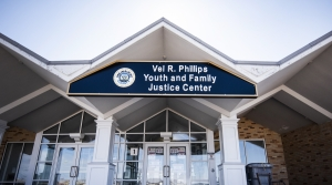 A building with a zig-zagging roof has a sign with the name of the juvenile justice center.