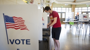 A voter in a red t-shirt fills out a ballot.