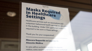 """A sign taped on a glass door says """"Masks Required in Healthcare Settings."""""""