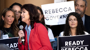 Rebecca Kleefisch speaks into a microphone on stage. People behind her hold campaign signs.