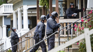 Officers in uniform climb steps to reach the front doors of homes.