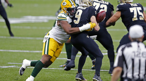 New Orleans Saints quarterback Drew Brees loses the ball as he is hit by Green Bay Packers linebacker Delontae Scott
